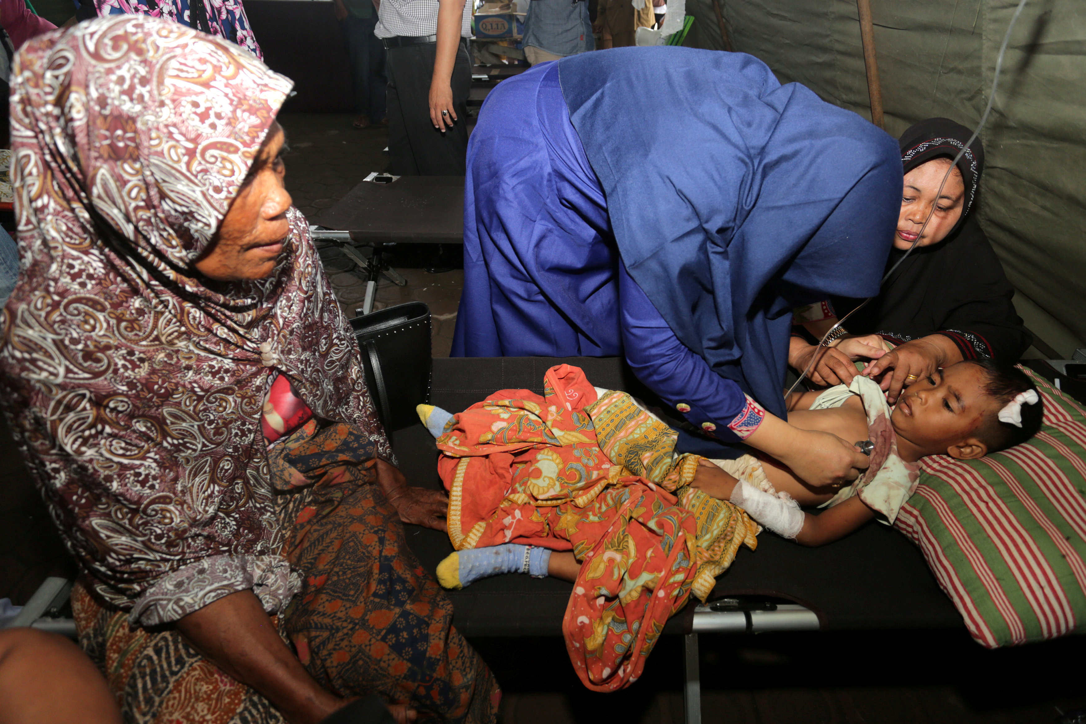 A medical officer checks the condition of an injured child at a hospital following an earthquake in Sigli, Pidie regency, in the northern province of Aceh, Indonesia