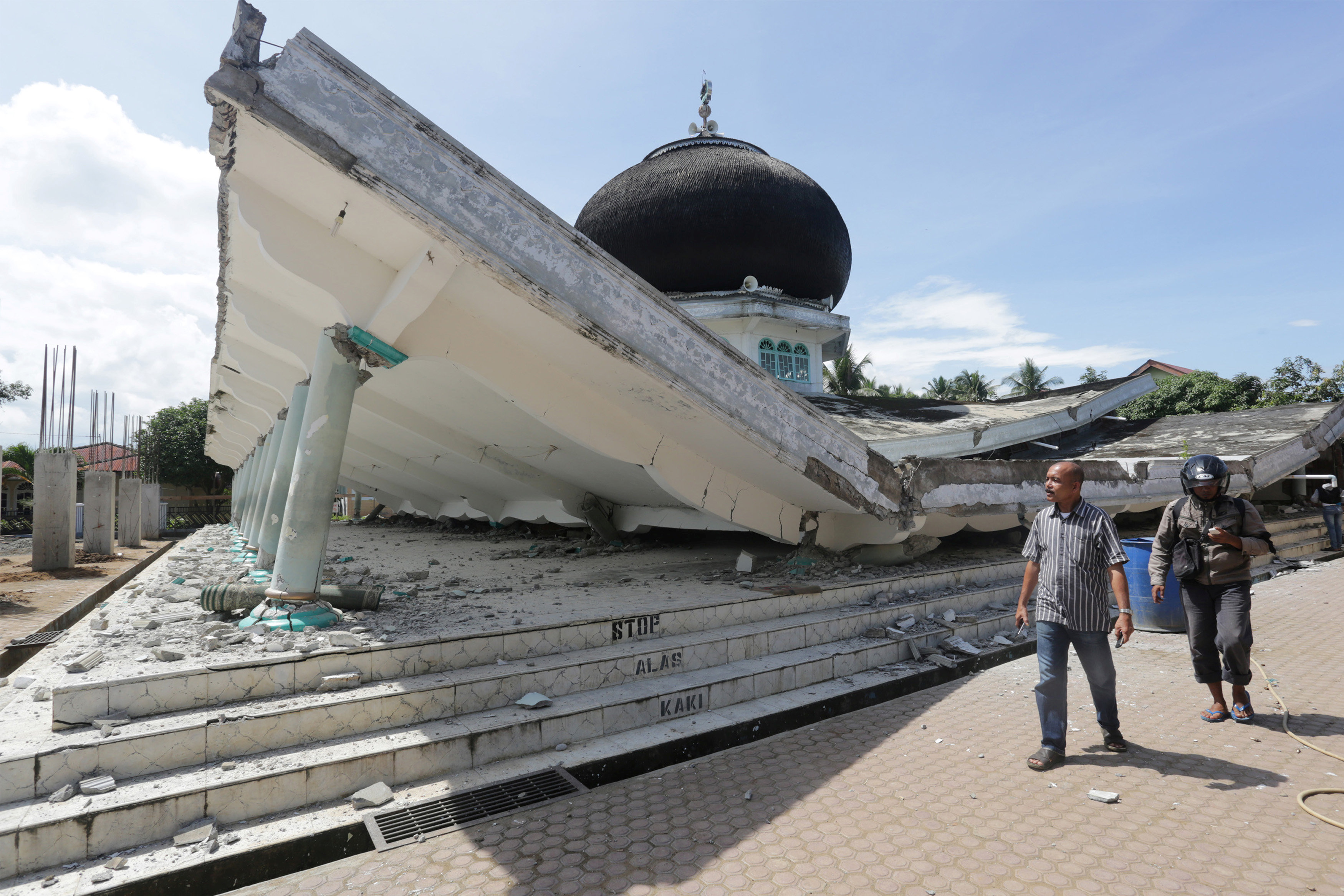 People walk near a collapsed mosque following an earthquake in Meuredu, Pidie Jaya in the northern province of Aceh, Indonesia