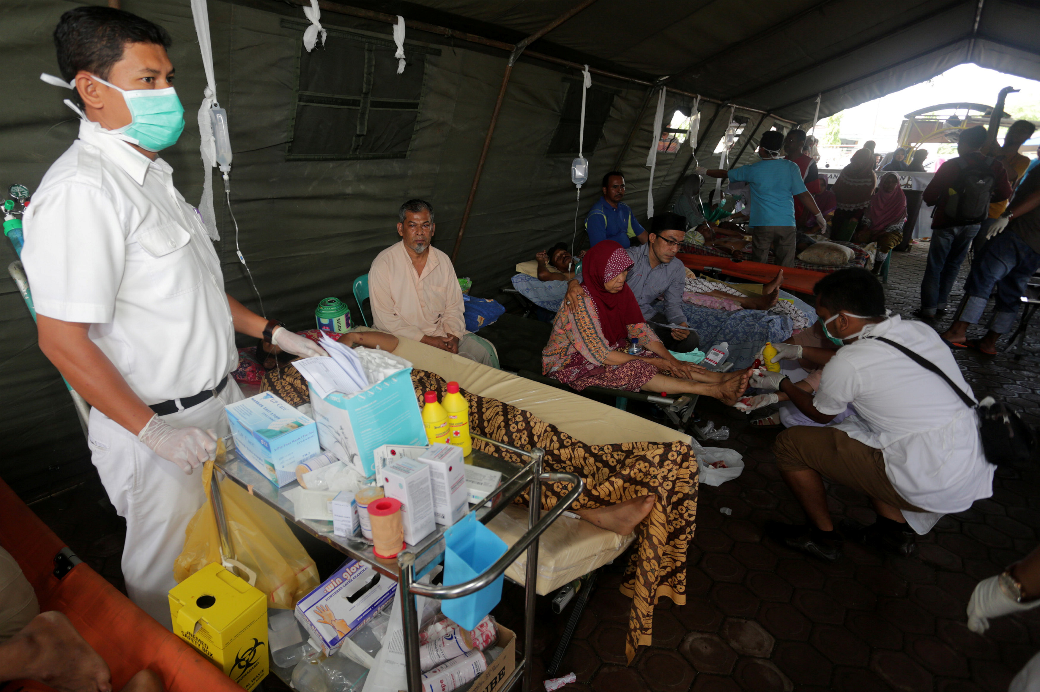 Injured people receive medical attention in an emergency tent at a hospital following an earthquake in Sigli, Pidie regency, in the northern province of Aceh, Indonesia