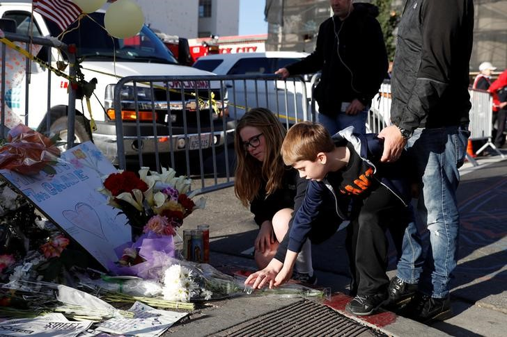 Two children place flowers at a makeshift memorial near the scene of the fatal warehouse fire in Oakland, California