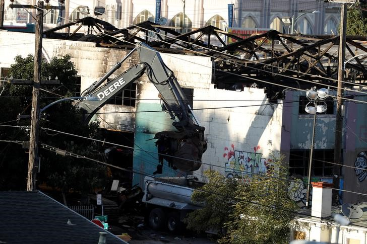 A crane removes debris from the site of a fatal warehouse fire in Oakland, California, U.S.