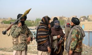 Members of the Taliban gather at the site of the execution of three men accused of murdering a couple during a robbery in Ghazni province, Afghanistan