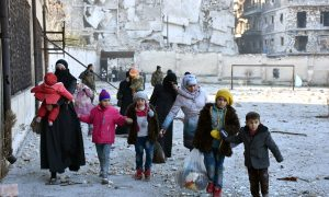 Civilians, who evacuated the eastern districts of Aleppo, carry their belongings as they arrive in a government held area of Aleppo, Syria,