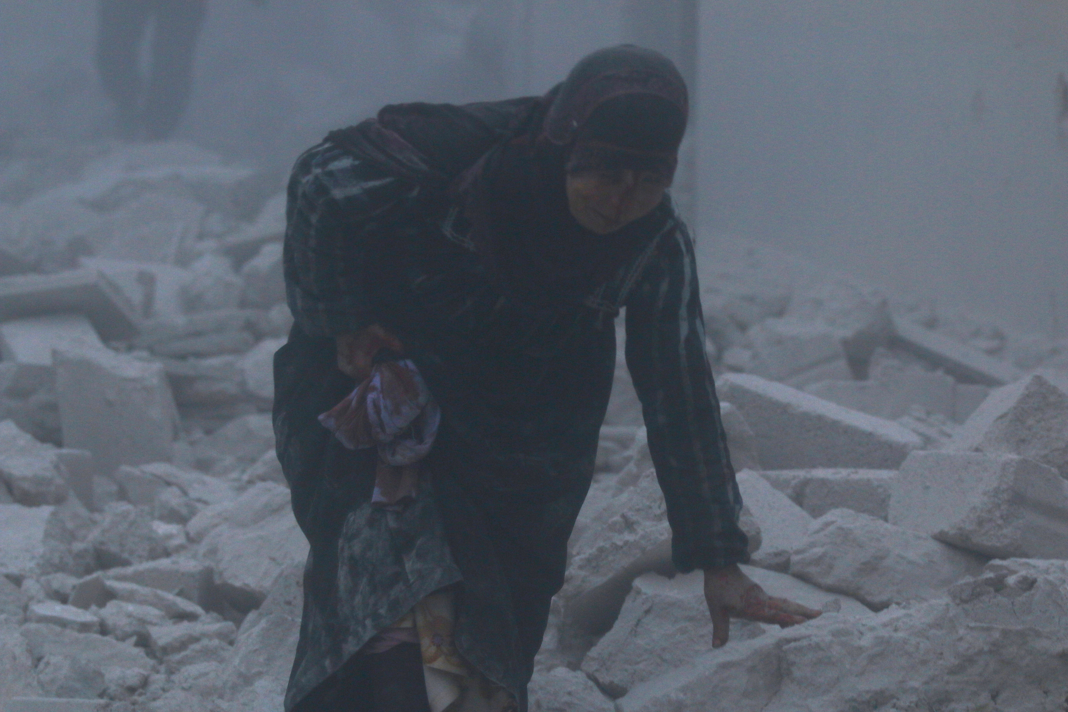 An injured woman walks at a site hit by an airstrike in the rebel-held al-Ansari neighbourhood of Aleppo, Syria
