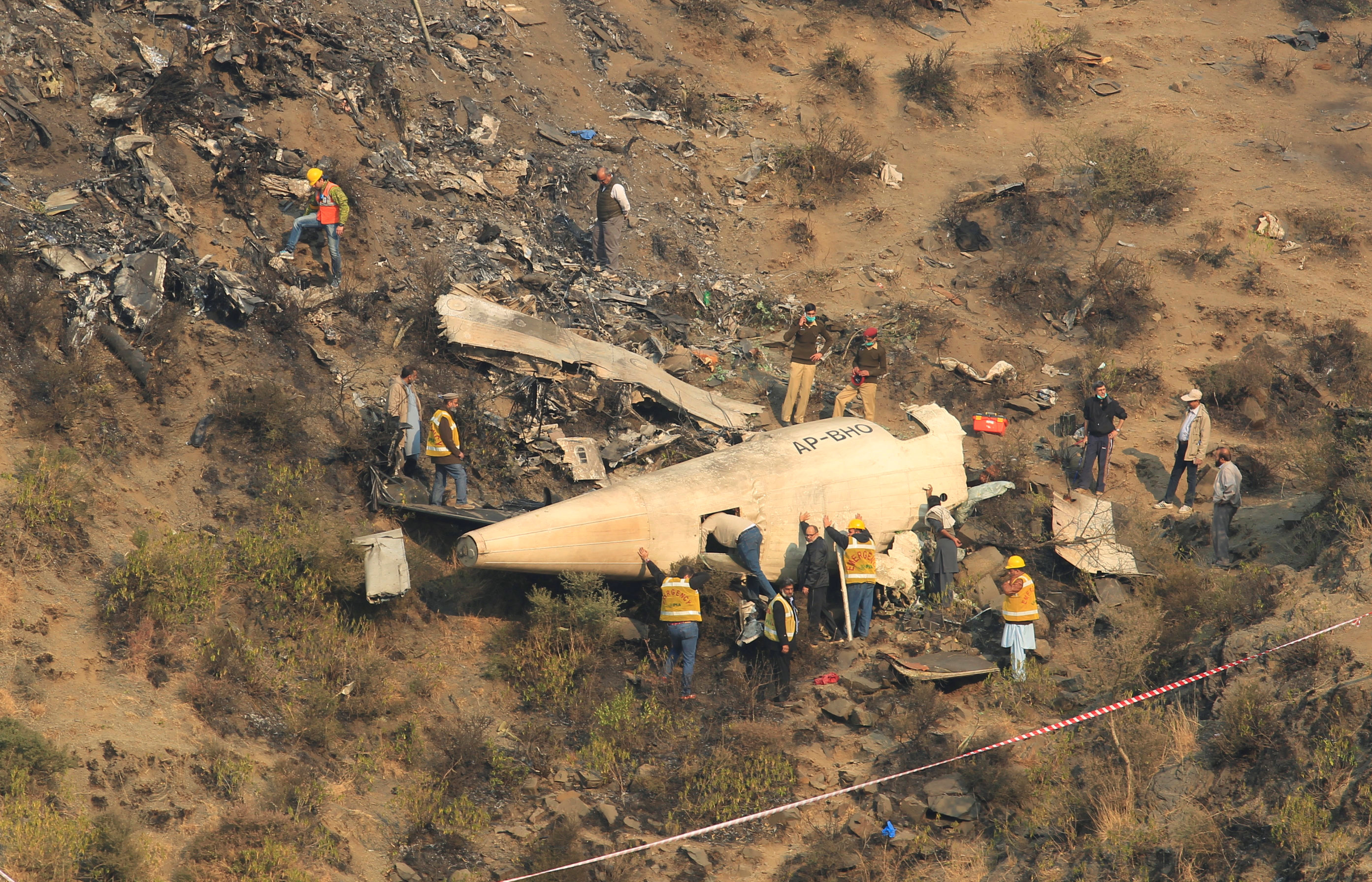 Rescue workers survey the site of a plane crashed a day earlier near the village of Saddha Batolni, near Abbotabad, Pakistan,