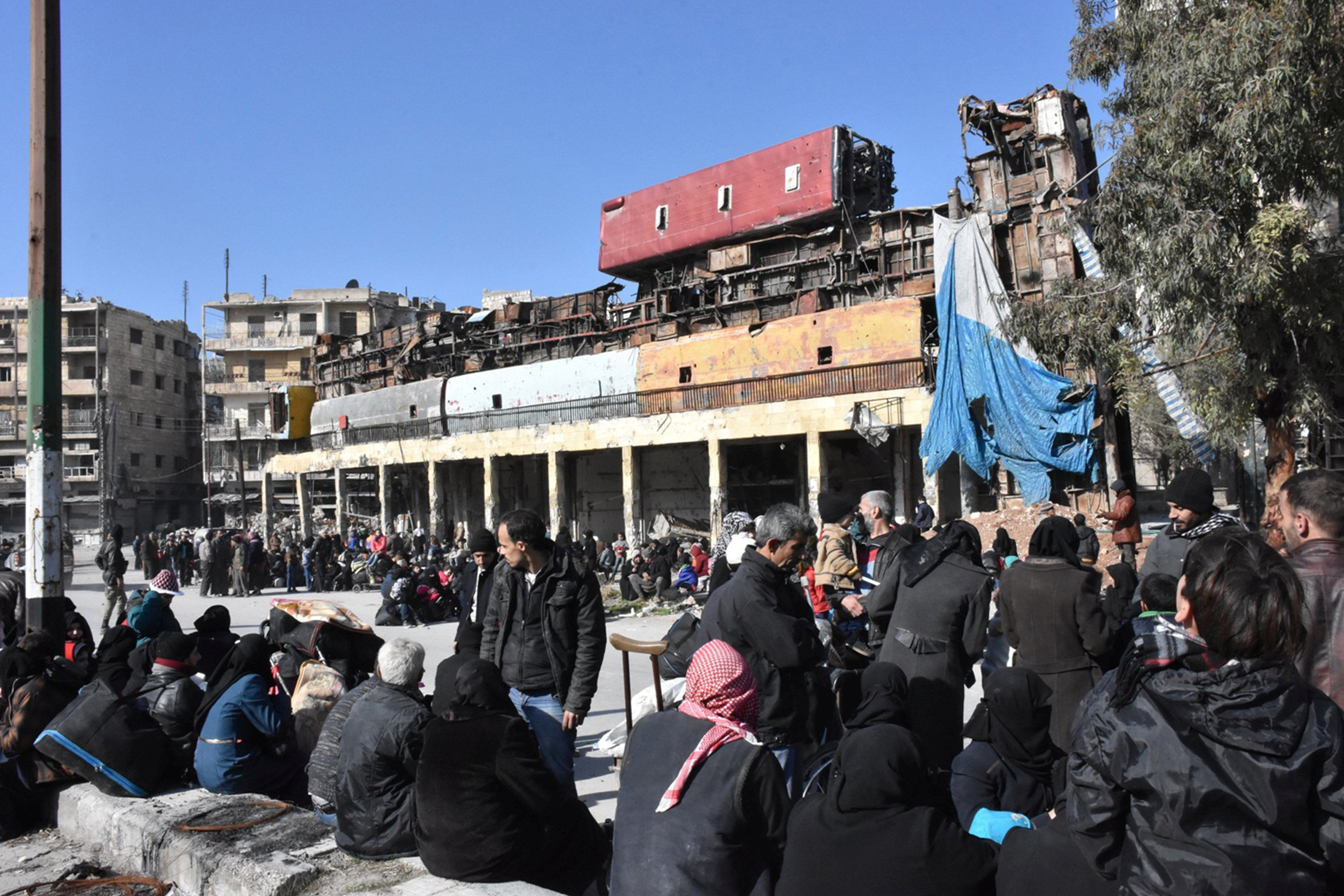 People, who were evacuated from the eastern districts of Aleppo, wait with their belongings in a government held area of Aleppo, Syria,