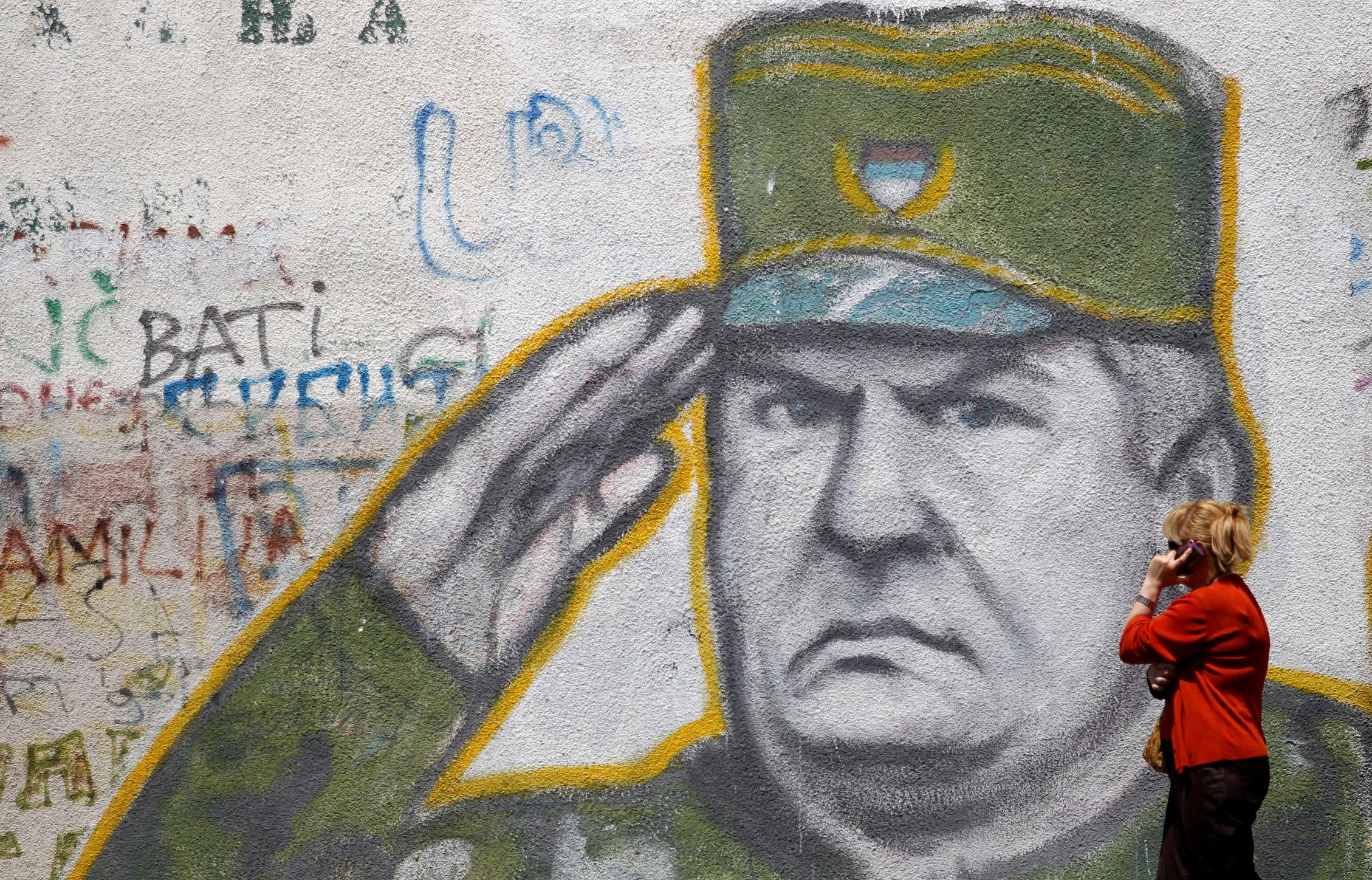 A woman walks past graffiti of Bosnian Serb wartime general Ratko Mladic in a suburb of Belgrade, Serbia,