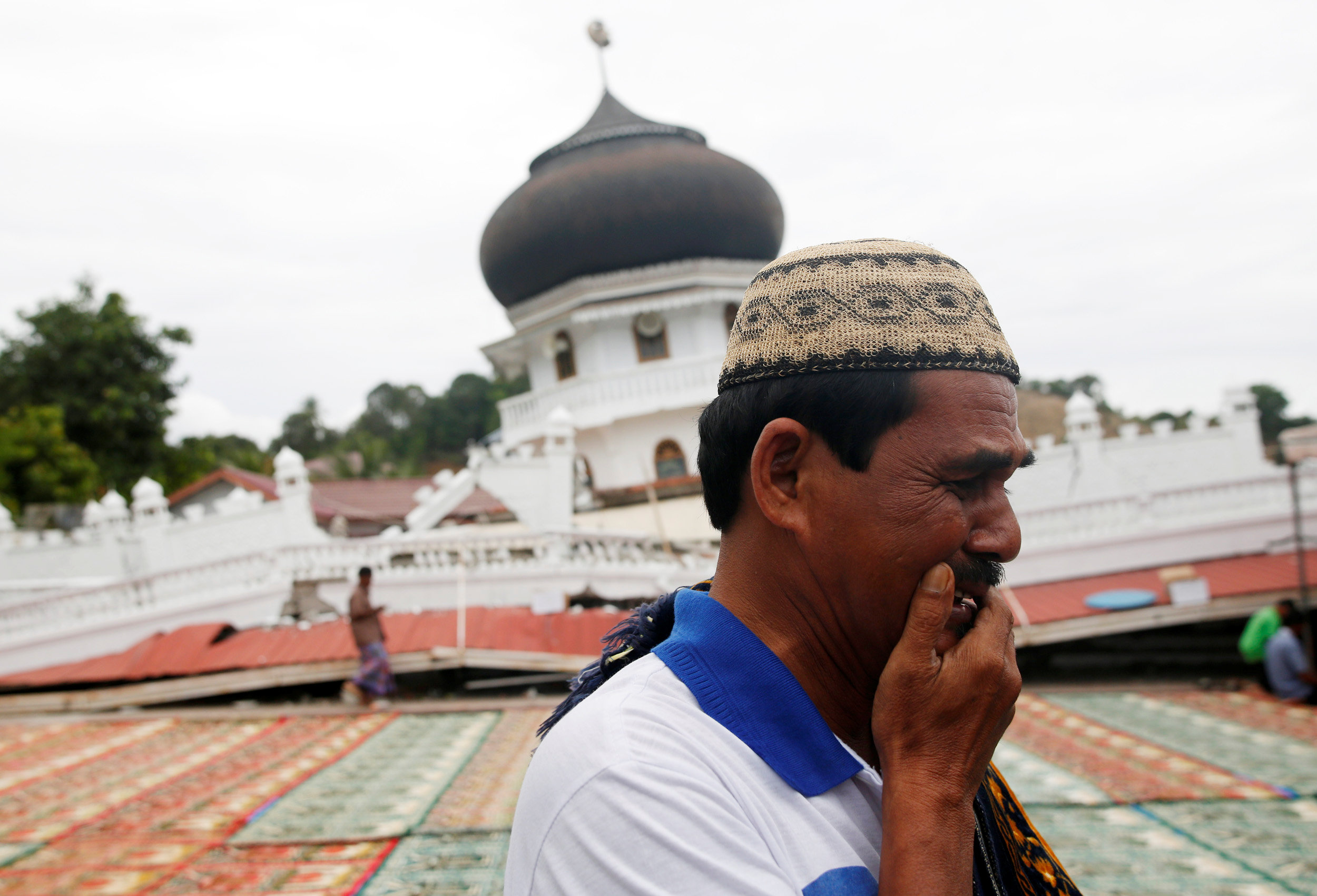 A Muslim man weeps as he arrives for Friday prayers at Jami Quba mosque which collapsed during this week's earthquake in Pidie Jaya, Aceh province, Indonesia
