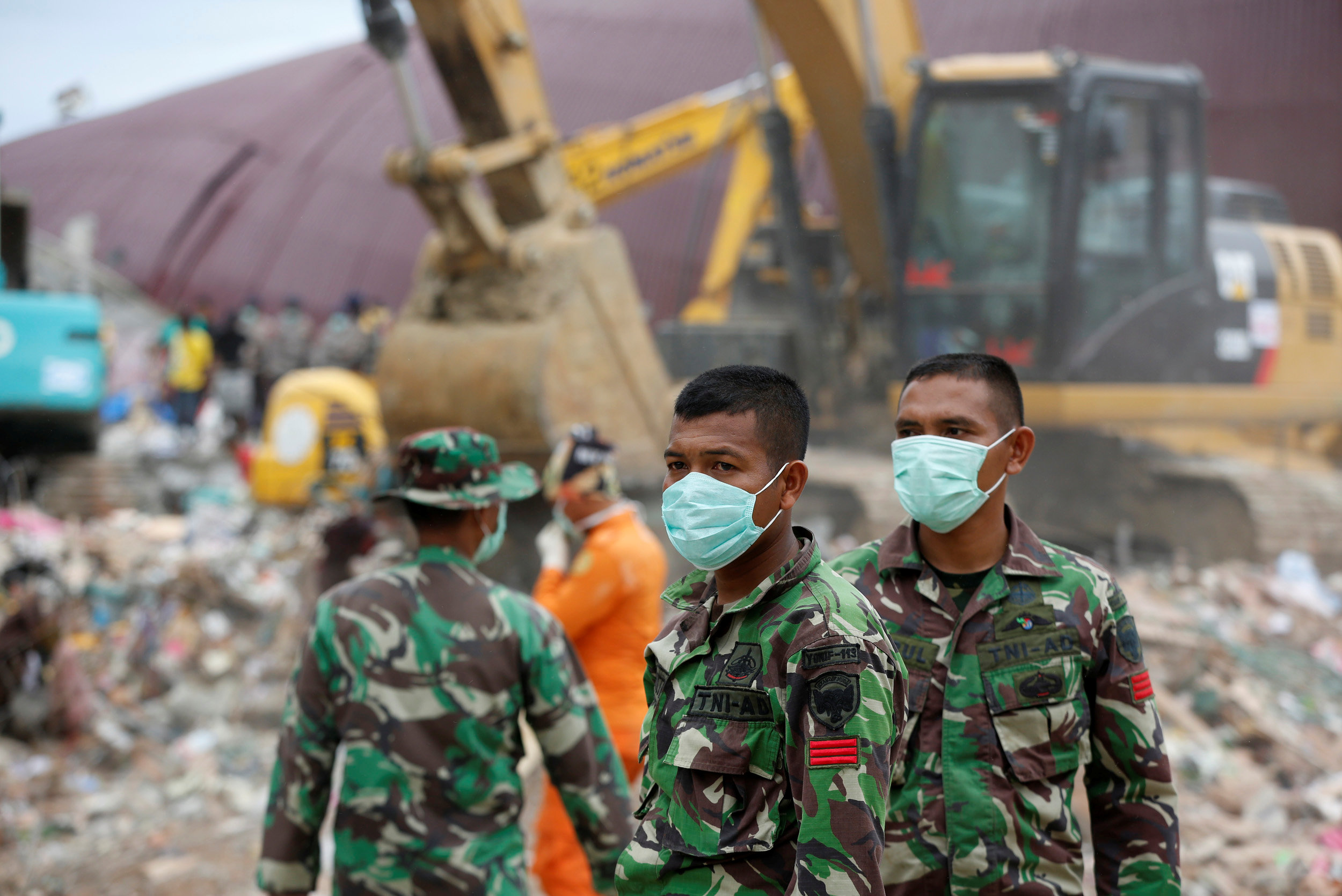 Indonesian soldiers help to secure an area where rescue and salvage operations take place at a collapsed building following this week's strong earthquake in Meureudu, Pidie Jaya, Aceh province, Indonesia