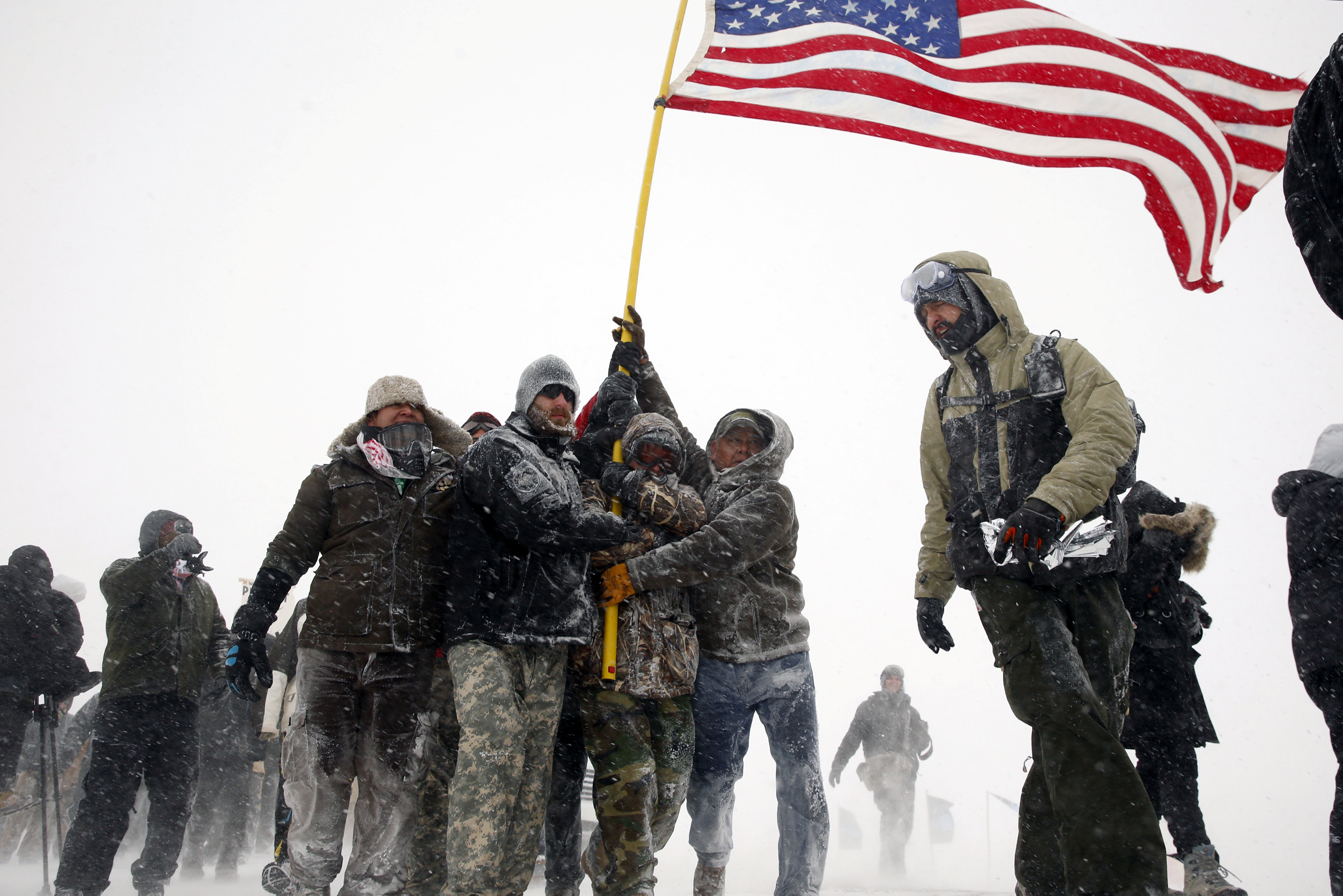 "Veterans join activists in a march to Backwater Bridge just outside of the Oceti Sakowin camp during a snow fall as ""water protectors"" continue to demonstrate against plans to pass the Dakota Access pipeline adjacent to the Standing Rock Indian Reservation, near Cannon Ball, North Dakota, U.S."