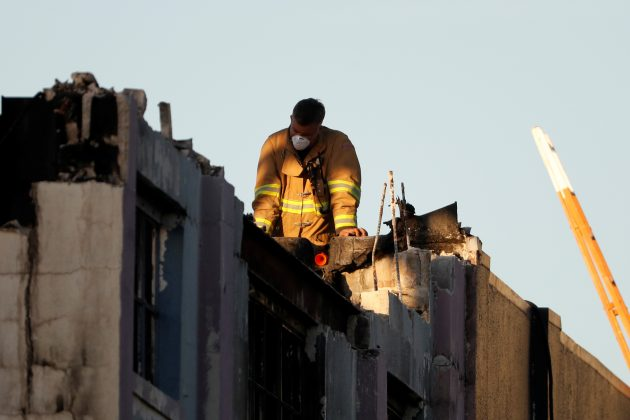 A firefighter watches from the roof at the scene of the fatal warehouse fire in Oakland, California, U.S.