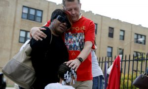 "Father Michael Pfleger comforts Lutrice Boyd and her granddaughter Faith Davis during a news conference by ""Purpose over Pain"", a group of mothers who lost children to gun violence, calling for a stop to shootings in Chicago, Illinois,"