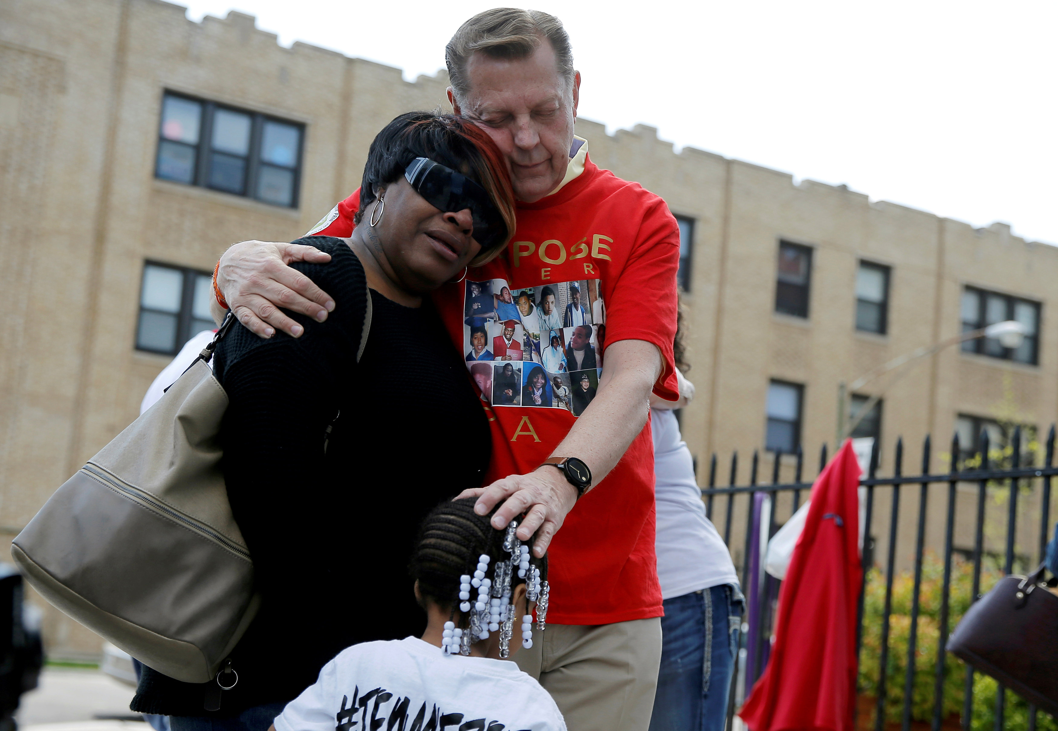 """Father Michael Pfleger comforts Lutrice Boyd and her granddaughter Faith Davis during a news conference by """"Purpose over Pain"""", a group of mothers who lost children to gun violence, calling for a stop to shootings in Chicago, Illinois,"""