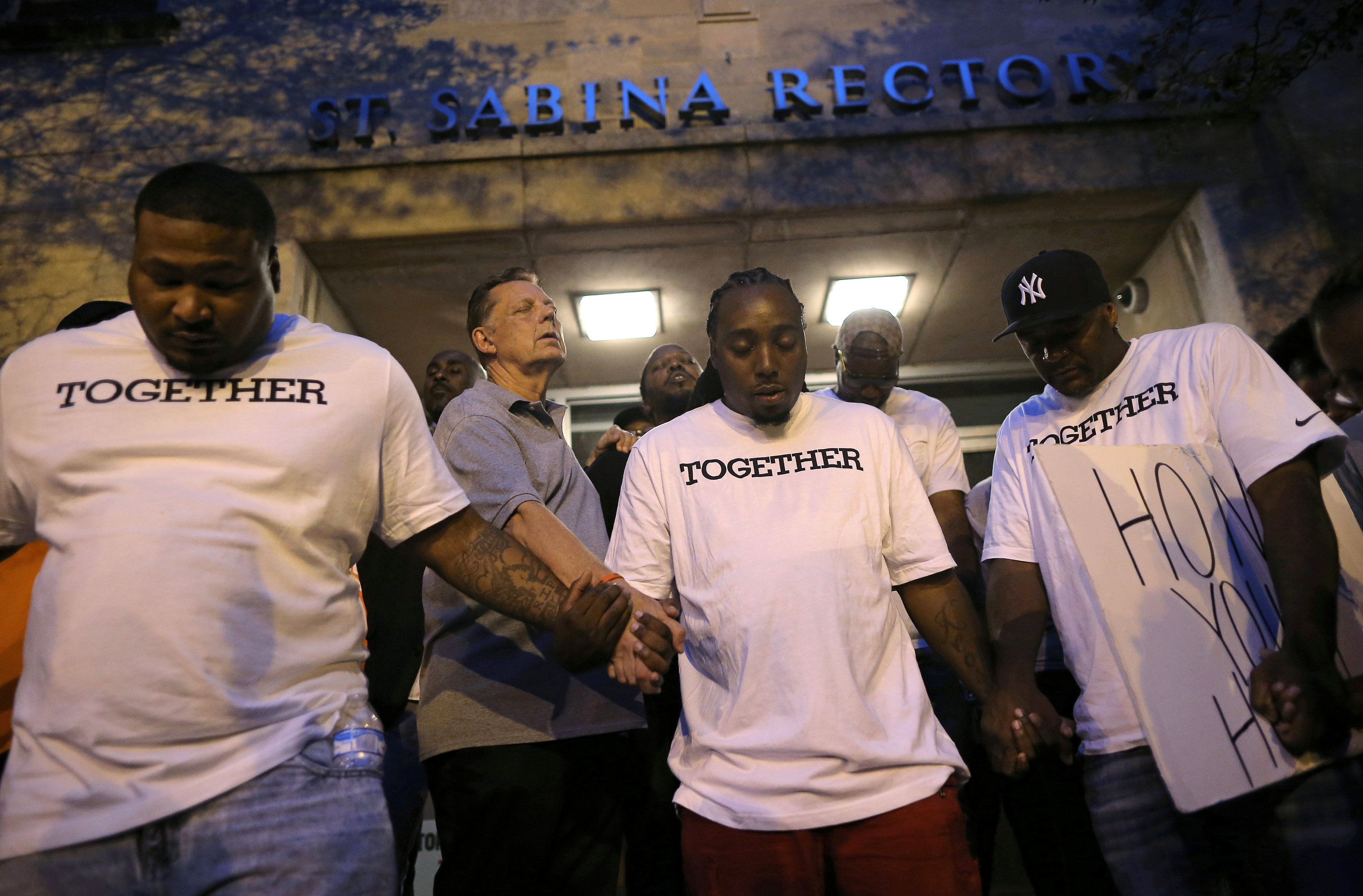 Father Michael Pfleger (2nd L) prays at Saint Sabina Church before taking part in a weekly night-time peace march through the streets of a South Side neighborhood in Chicago, Illinois,