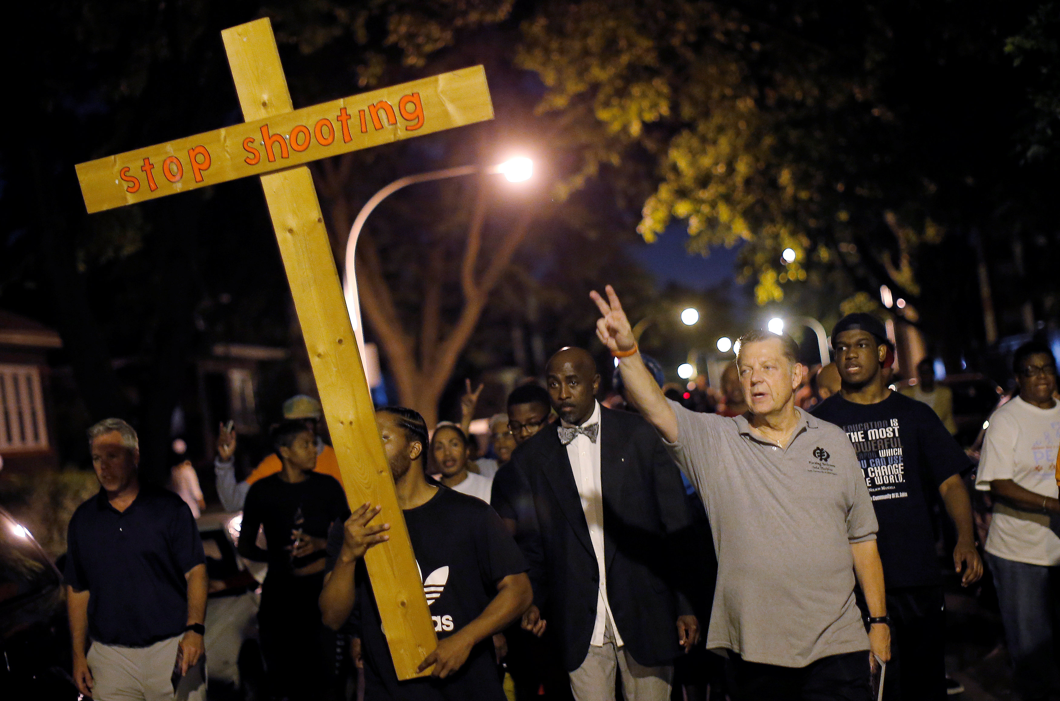 Father Michael Pfleger (3rd R) marches through the streets of a South Side neighborhood during a weekly night-time peace demonstration in Chicago, Illinois,