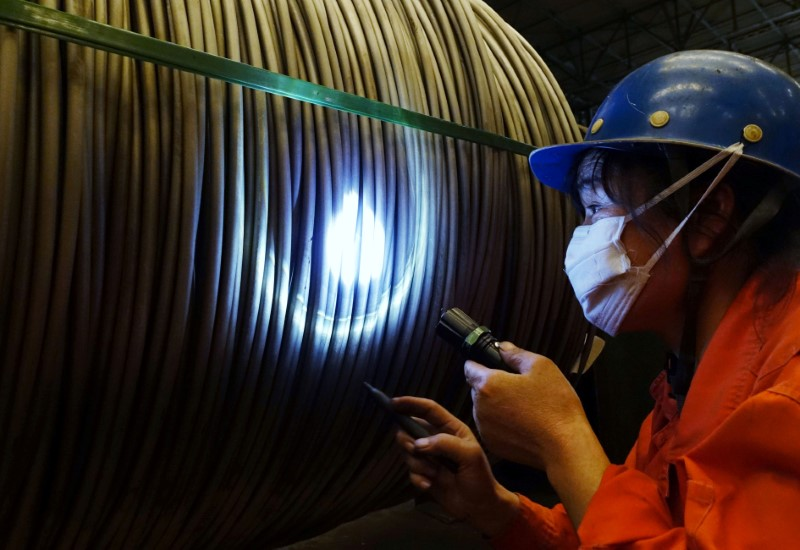 A worker verifies a product at a steel factory in Dalian, Liaoning province, China