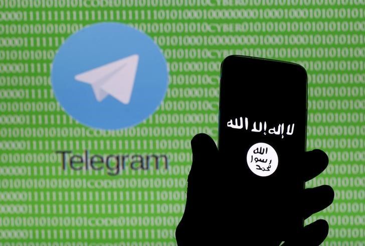 A man holds a smartphone showing the Islamic State logo in front of a screen showing the Telegram logo in this picture illustration taken in Zenica, Bosnia and Herzegovina