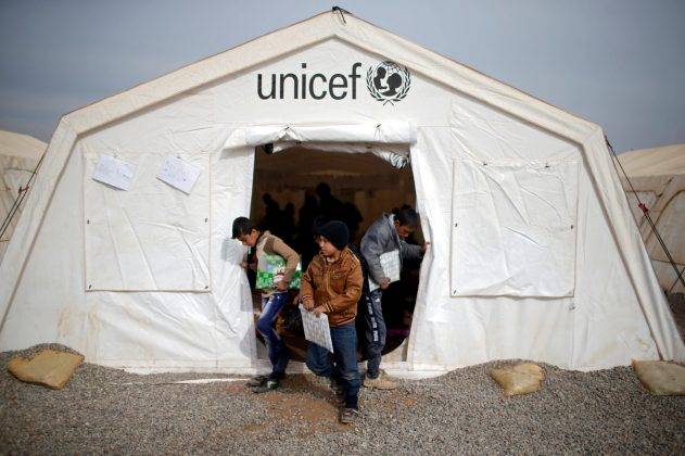 Displaced Iraqi boys leave a tent school set by United Nations Children's Fund (UNICEF) at Hassan Sham camp, east of Mosul, Iraq