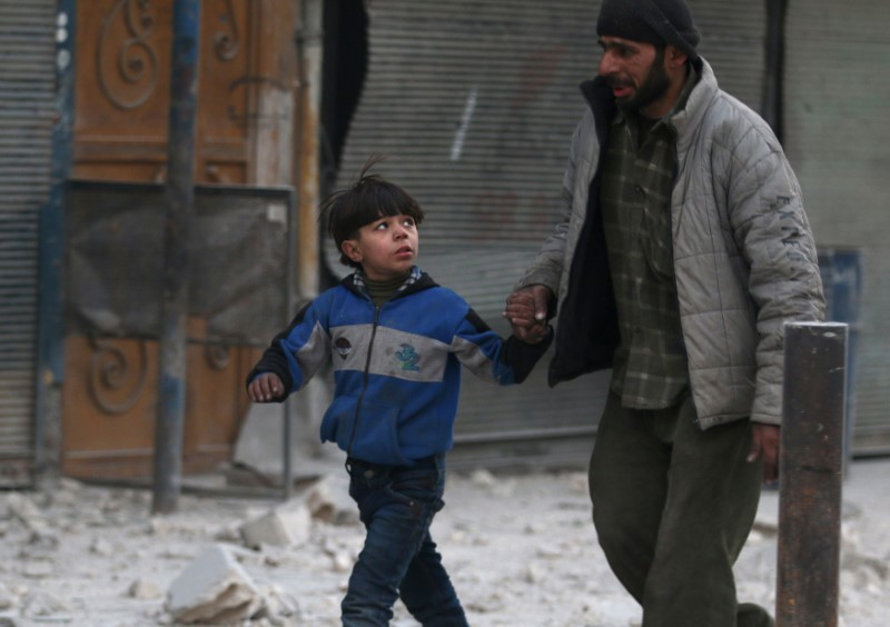 A man holds the hand of a boy as they flee deeper into the remaining rebel-held areas of Aleppo,