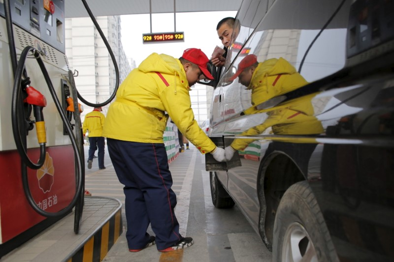 A gas station attendant pumps fuel into a customer's car at PetroChina's petrol station in Beijing, China,