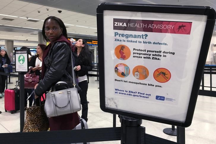 A woman looks at a Center for Disease Control (CDC) health advisory sign about the dangers of the Zika virus as she lines up for a security screening at Miami International Airport in Miami, Florida,