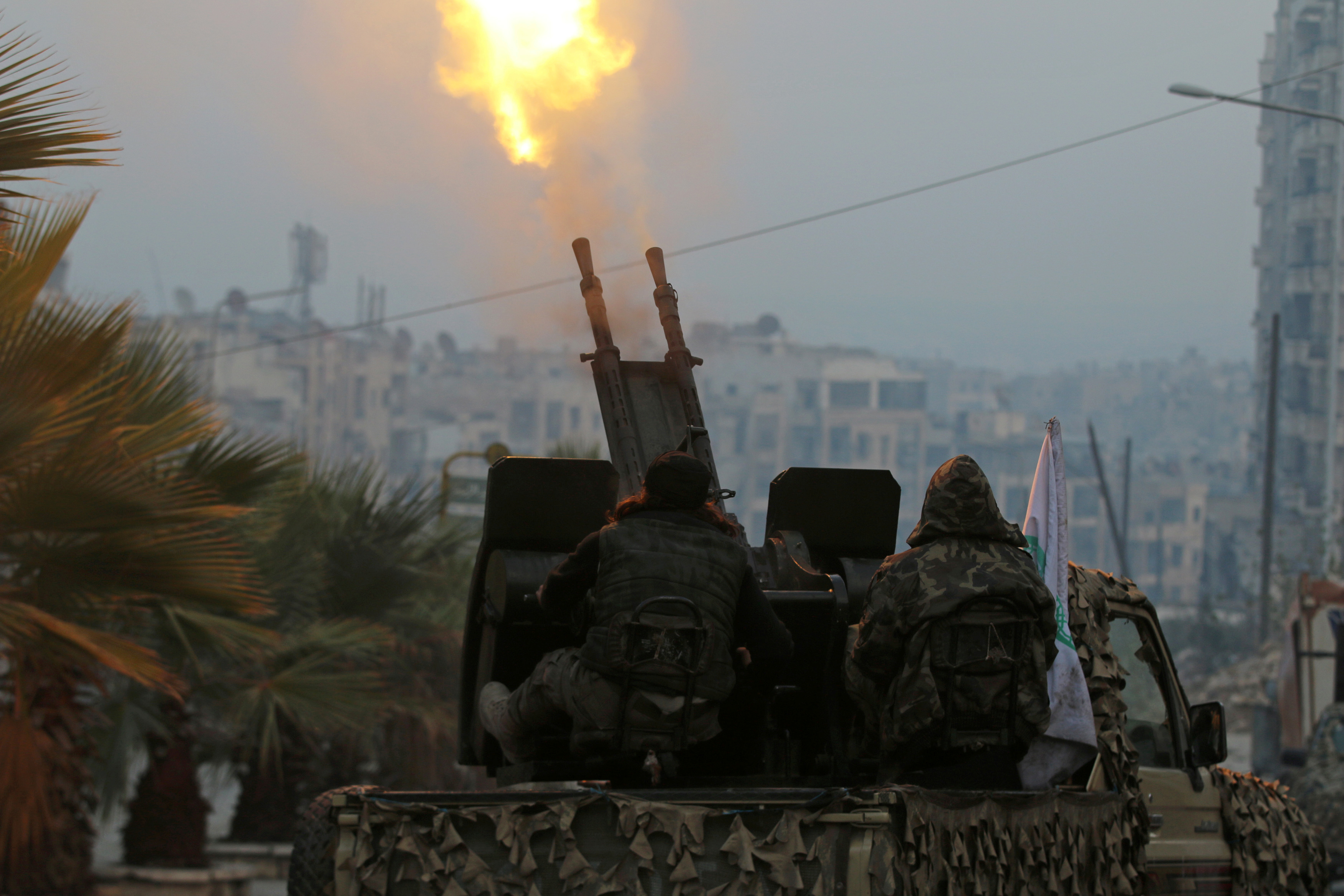 Free Syrian Army fighters fire an anti-aircraft weapon in a rebel-held area of Aleppo, Syria.