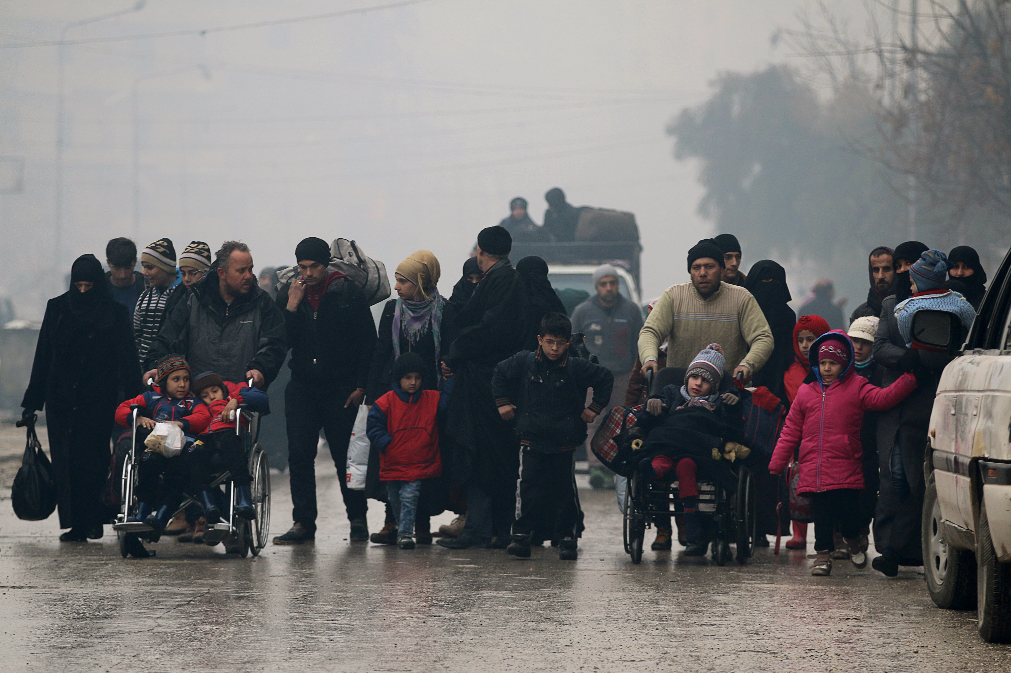 People walk as they flee deeper into the remaining rebel-held areas of Aleppo, Syria