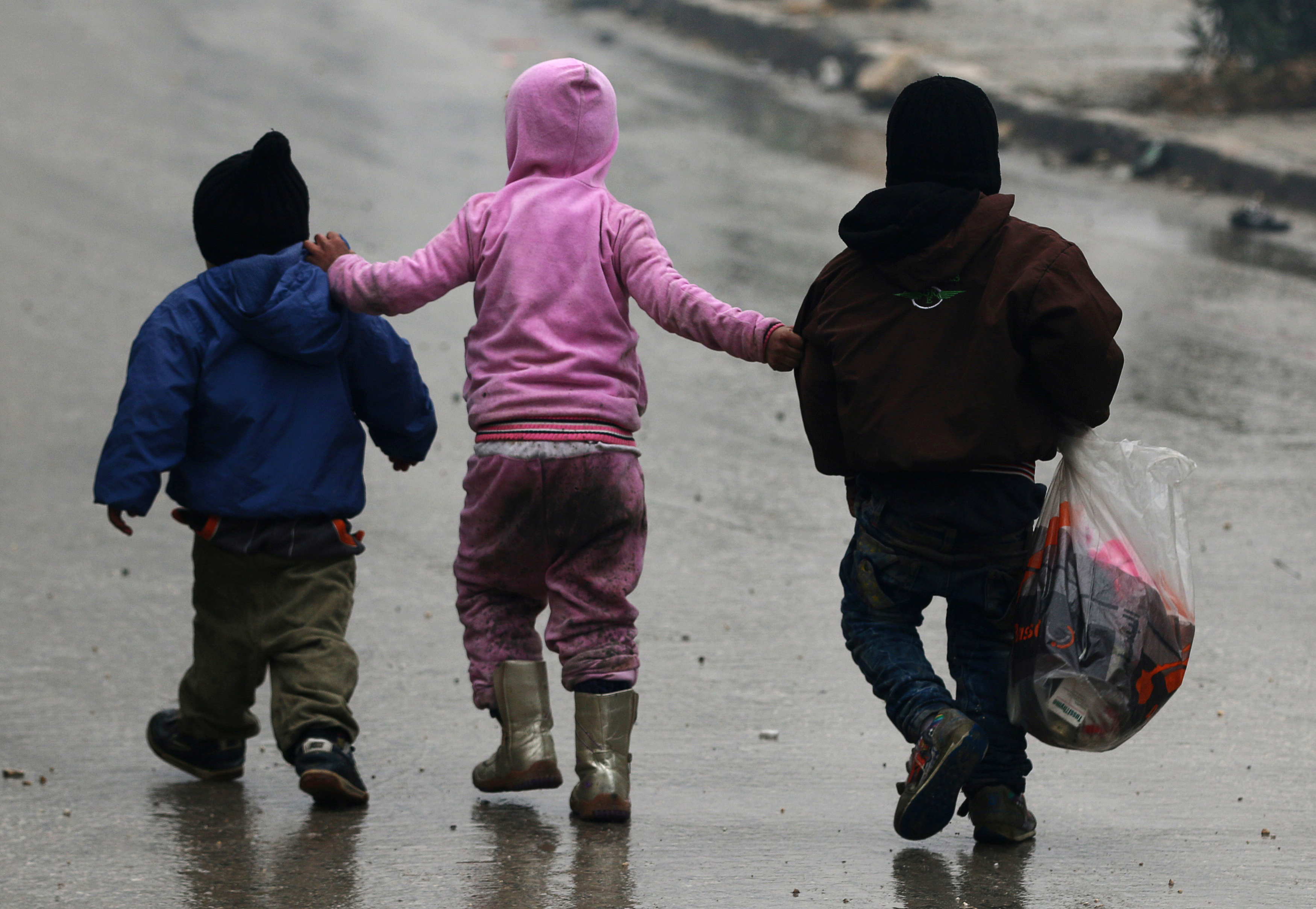 Children walk together as they flee deeper into the remaining rebel-held areas of Aleppo, Syria