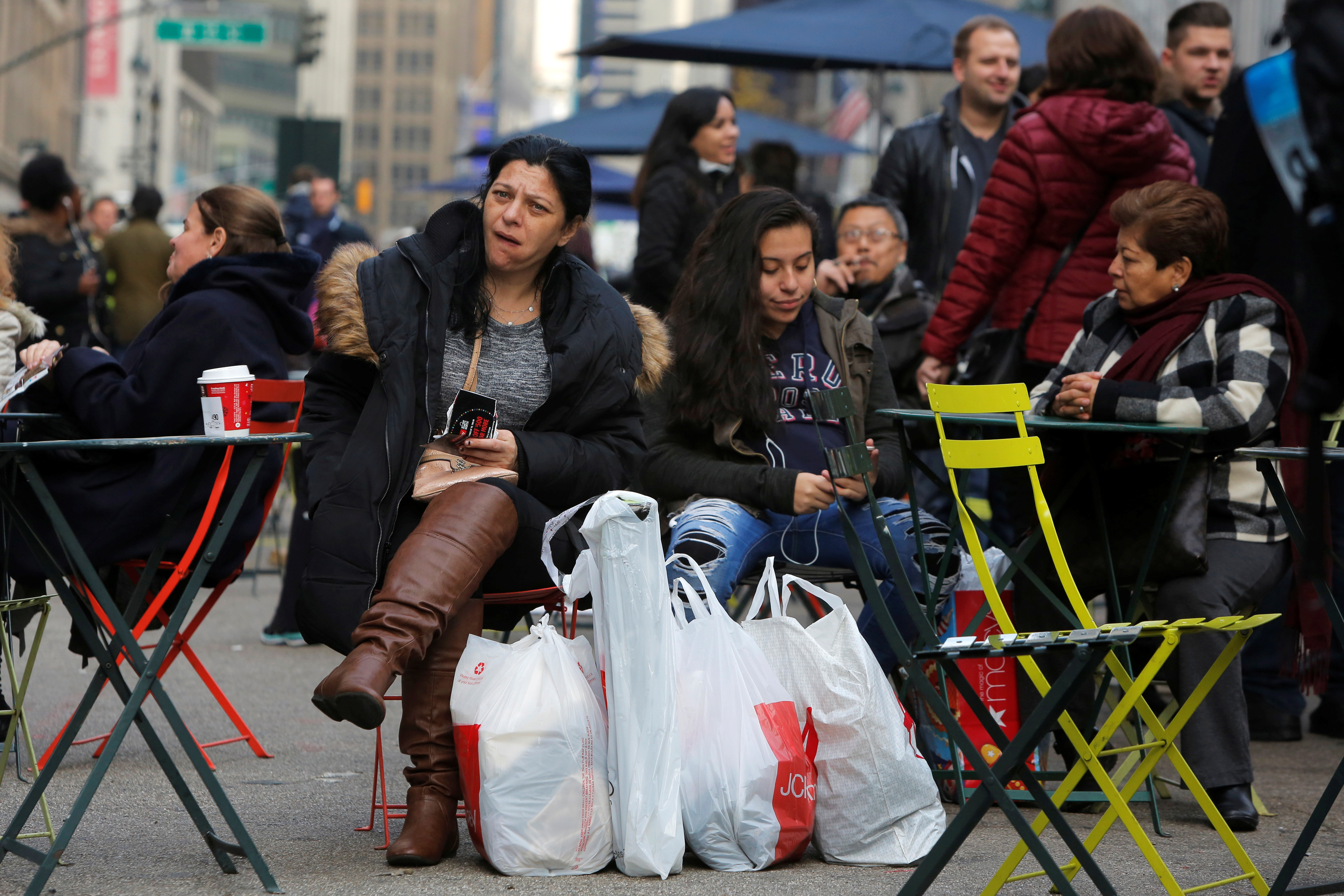 A woman sits in Herald Square with bags of shopping during Black Friday sales in Manhattan, New York,