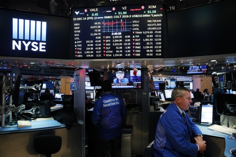 A trader works on the floor of the New York Stock Exchange (NYSE) as a television screen displays coverage of U.S. Federal Reserve Chairman Janet Yellen shortly after the announcement that the U.S. Federal Reserve will hike interest rates, in New York, U.S.,