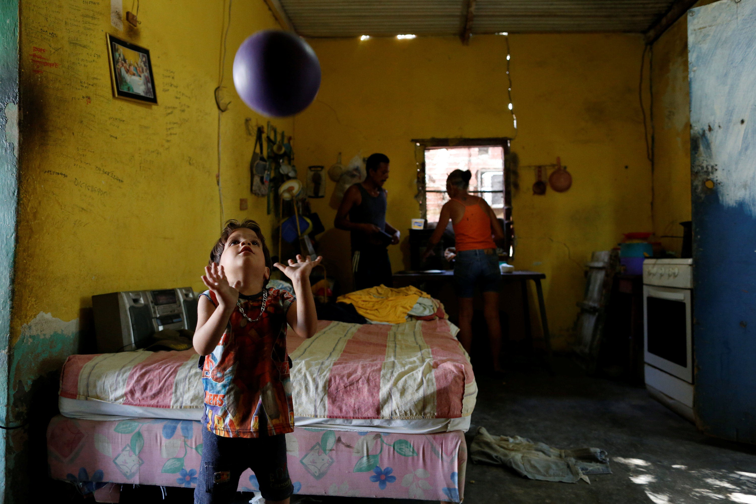 Emmanuel Cuauro, 4, plays with a ball next to his parents Zulay Pulgar (R), 43, and Maikel Cuauro, 30, in their house in Punto Fijo, Venezuela