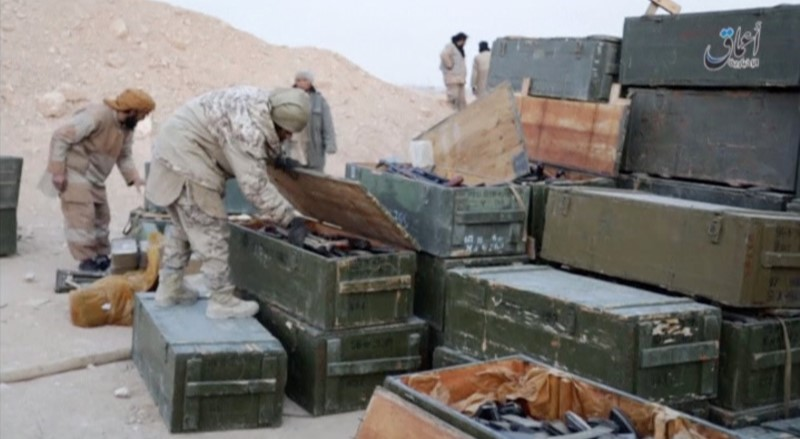Islamic State fighters search weapon boxes in a Russian base in what is said to be Palmyra,