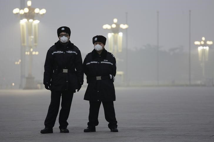 Policemen wear protective masks at the Tiananmen Square on an extremely polluted day as hazardous, choking smog continues to blanket Beijing, China