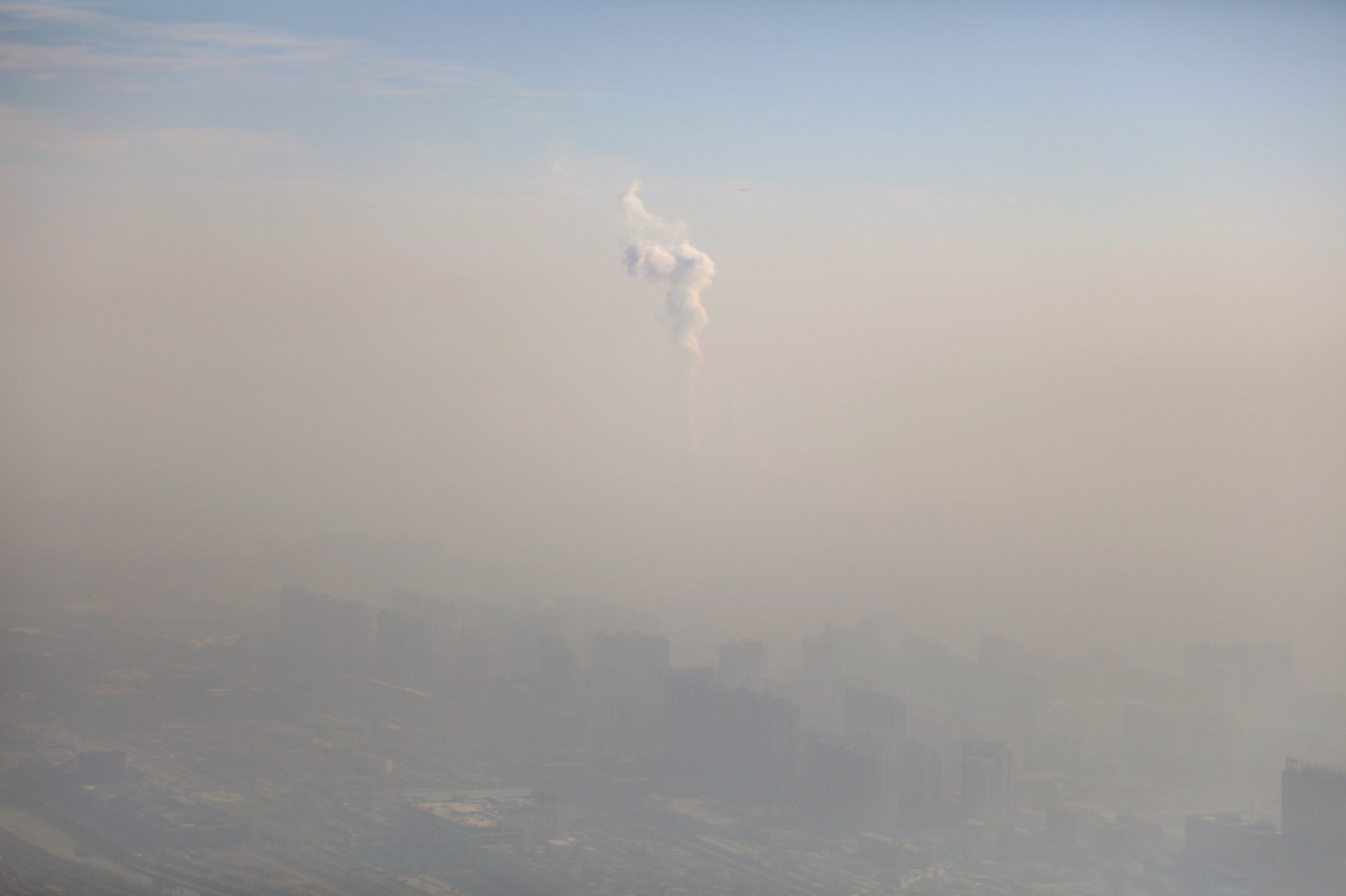 A chimney of a power plant is pictured among smog as a red alert for air pollution is issued in Beijing, China,