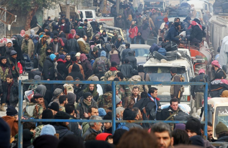 FILE PHOTO - Rebel fighters and civilians gather as they wait to be evacuated from a rebel-held sector of eastern Aleppo, Syria December