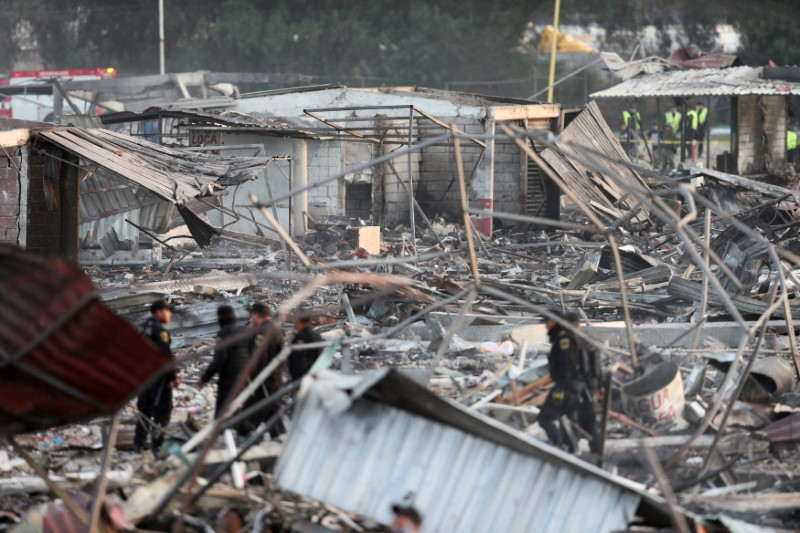 Police officers walk amongst the wreckage of houses destroyed in an explosion at the San Pablito fireworks market outside the Mexican capital on Tuesday, in Tultepec, Mexico,