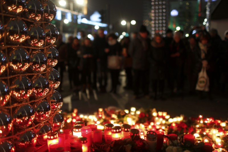 Candles burn at a Christmas market at Breitscheidplatz in Berlin, Germany, December 20, 2016, to commemorate the 12 victims of a truck that ploughed into the crowded market.