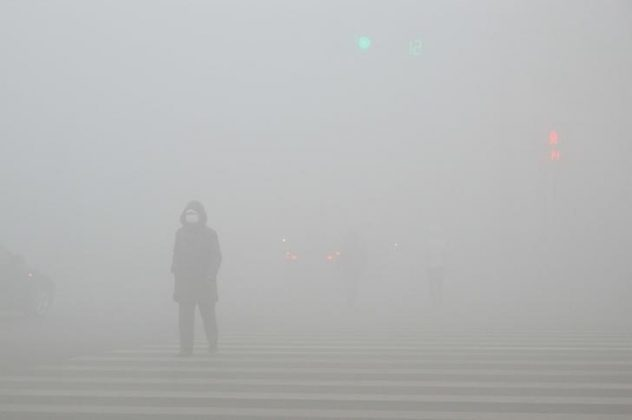 People walk past a street in heavy smog during a polluted day in Weifang, Shandong province,