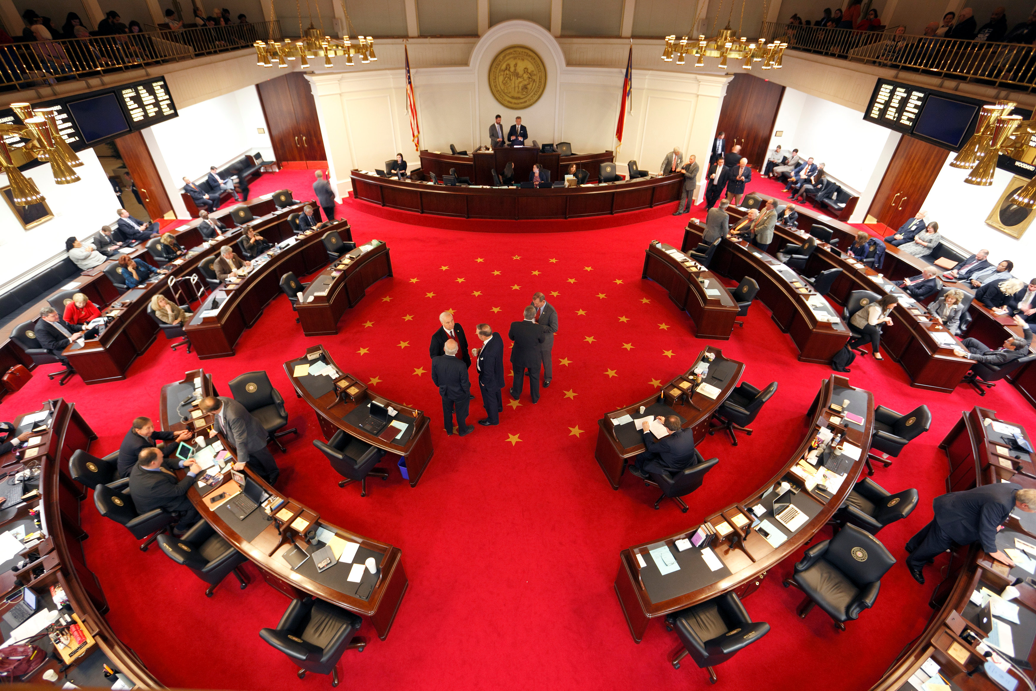 Lawmakers confer during a negotiations on the floor of North Carolina's State Senate chamber as they meet to consider repealing the controversial HB 2 law