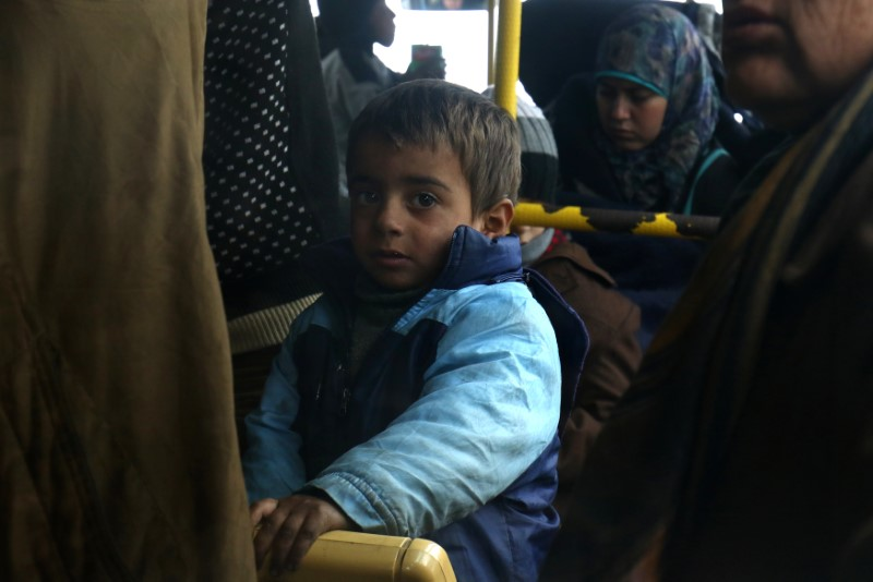 Evacuees from the Shi'ite Muslim villages of al-Foua and Kefraya ride a bus at insurgent-held al-Rashideen in Aleppo province, Syria