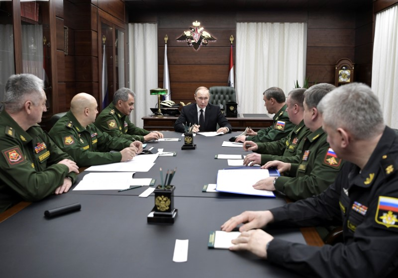 Russian President Vladimir Putin, Defence Minister Sergei Shoigu and chief of Russia's General Staff Valery Gerasimov attend a meeting with top military officials at the Defence Ministry in Moscow, Russia