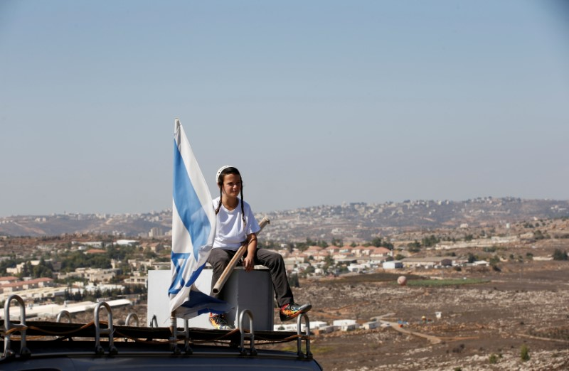 A boy sits near an Israeli flag atop the roof of a vehicle at the entrance to the Jewish settler outpost of Amona in the West Bank