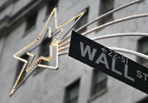 A holiday decoration is seen over Wall St. sign outside the New York Stock Exchange,