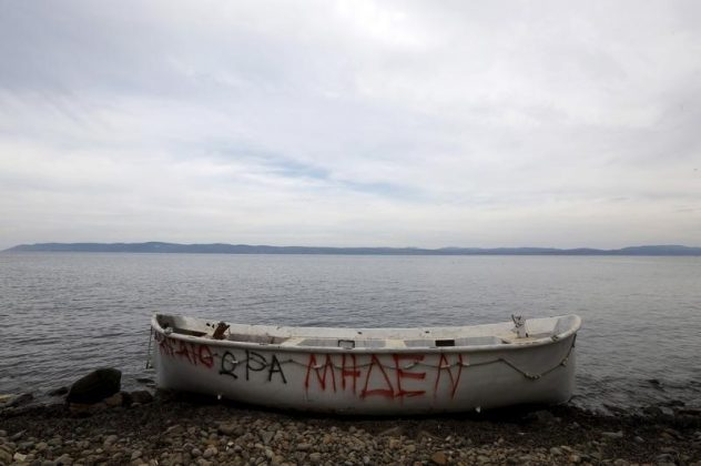 "A wooden boat, used by migrants and refugees, is abandoned at a beach on the Greek island of Lesbos November, 2015. The writing on the boat reads ""Aegean zero hour"""