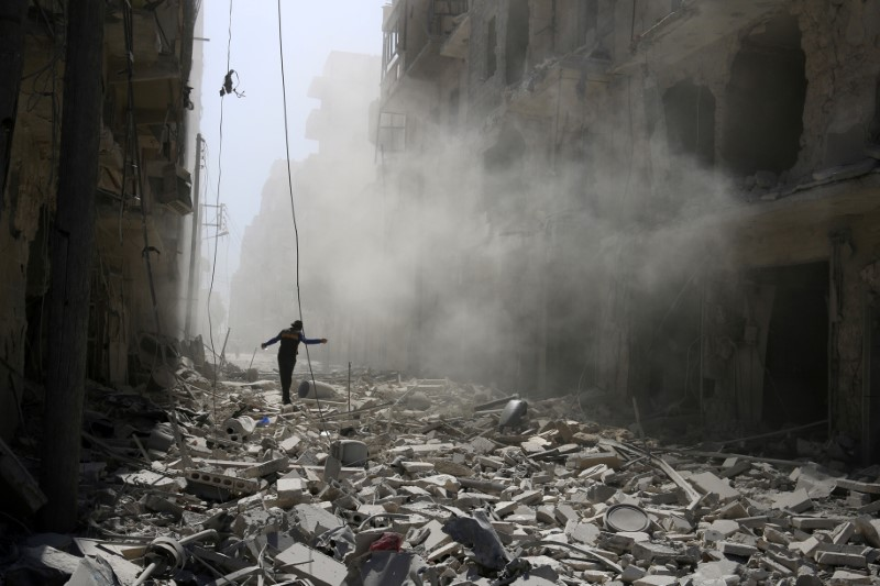 SYRIA: A man walks on the rubble of damaged buildings after an airstrike on the rebel held al-Qaterji neighbourhood of Aleppo, Syria