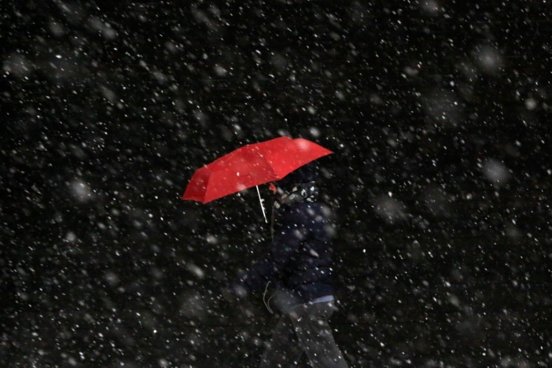 A person walks along Chambers Street during morning snow in Manhattan, New York City,