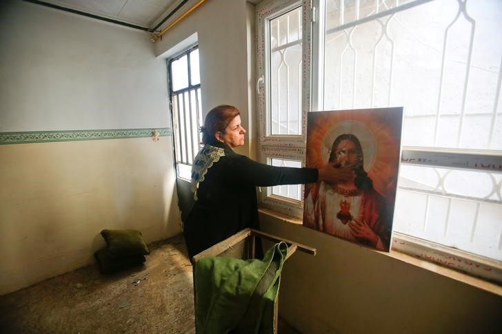 A Christian woman inspects a home in the town of Bartella east of Mosul, Iraq, after it was liberated from Islamic State militants