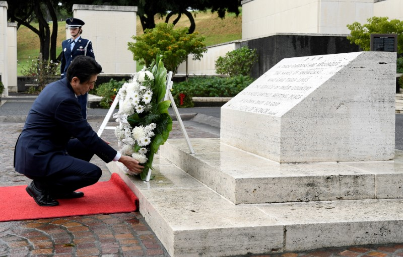 Japan's Prime Minister Shinzo Abe presents a wreath at the National Memorial Cemetery of the Pacific at Punchbowl in Honolulu, Hawaii, U.S.