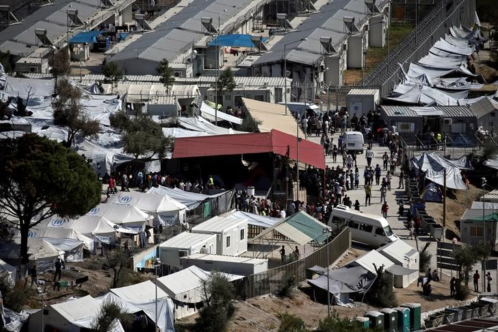 Refugees and migrants line up for food distribution at the Moria migrant camp