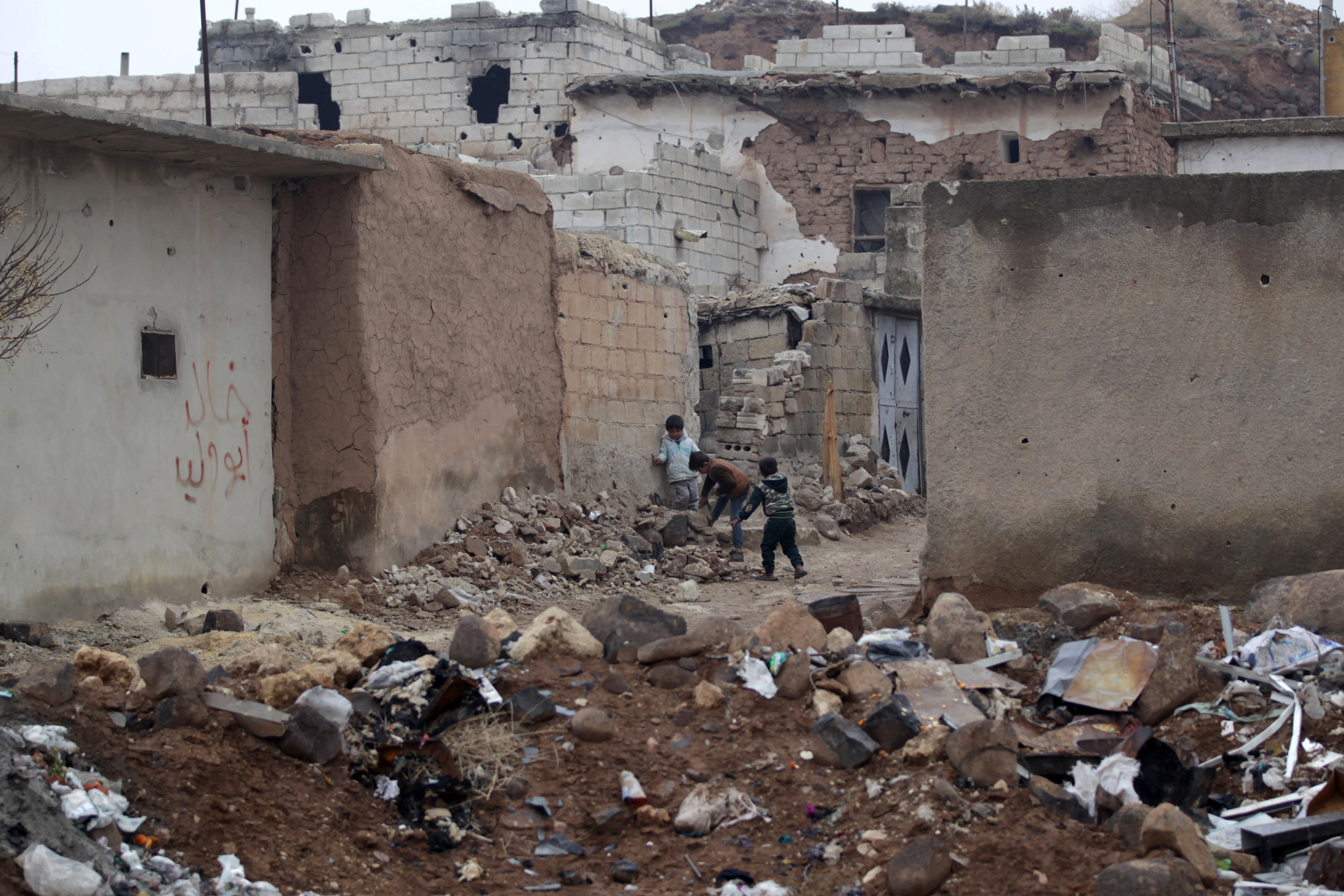 Children play near rubble of damaged buildings in al-Rai town, northern Aleppo countryside, Syria